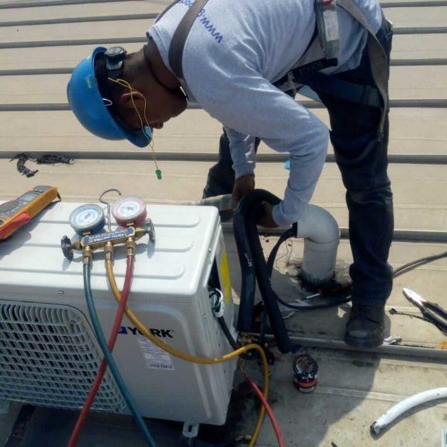 persona dando mantenimiento a aire acondicionado